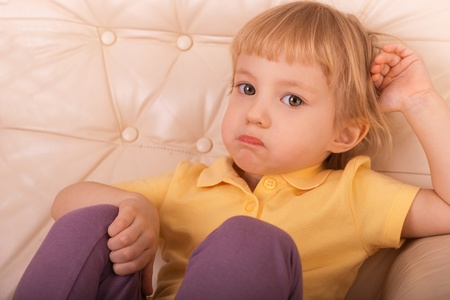 resentment: little girl sitting on couch with a look of resentment Stock Photo