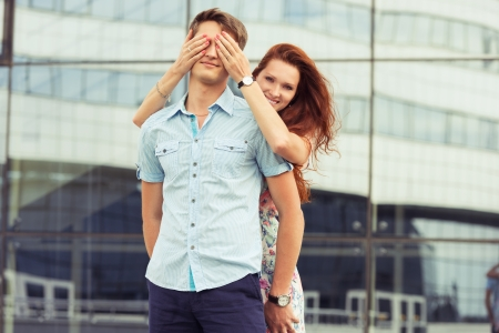 hands covering eyes: woman covering mans eyes hands. portrait couple at outdoor