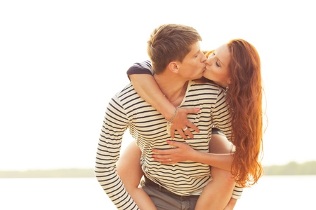 closeup kissing happy couple on beach. piggyback Stock Photo