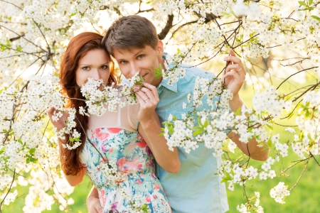 young family in flower garden. couple portrait photo