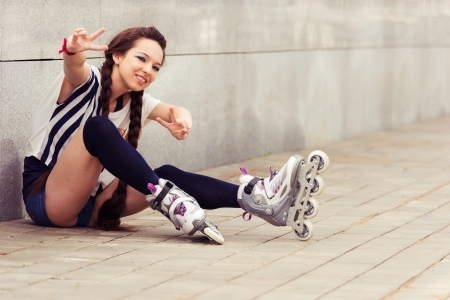 inline skater: happy teenager on rollerblading sitting on street  a sunny day. active lifestyle