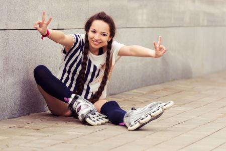 girl going rollerblading sitting putting on inline skates photo