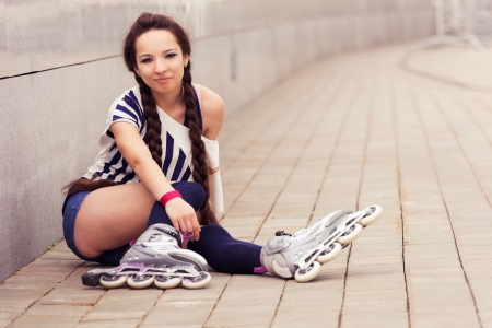 girl going rollerblading sitting putting on inline skates Stock Photo