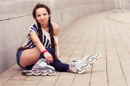 girl going rollerblading sitting putting on inline skates Stock Photo