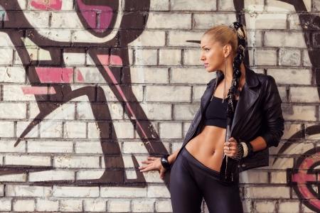 glam rock: fashion model in glam rock style on street near brick wall with graffiti