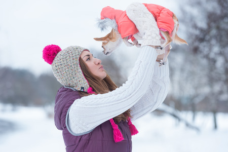 Young woman kissing little dog outdoors in winter park
