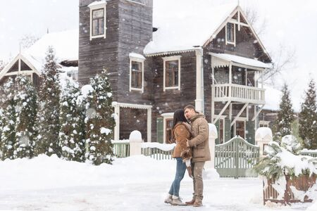 Beautiful  couple on background house. winter family outdoors photo