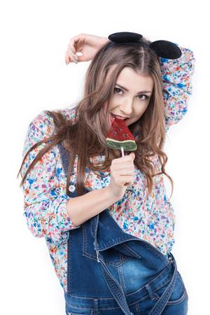 sucks: Young cheerful woman  sucks lollipop. Emotion and fun studio photo