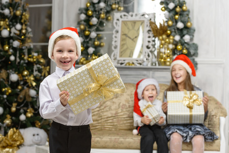 christmas family concept - happiness boy with x-mas gift box and smiling children Stock Photo