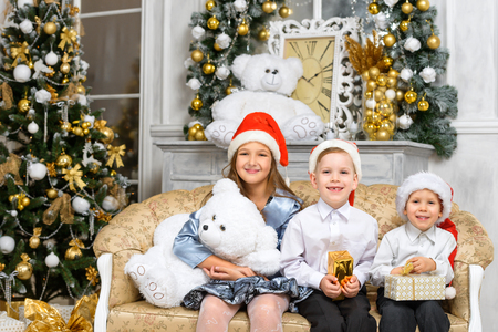 happiness christmas family concept - sisters and brothers with x-mas gift boxes Stock Photo