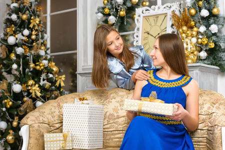 happiness christmas family concept - mother with gift boxes and daughter