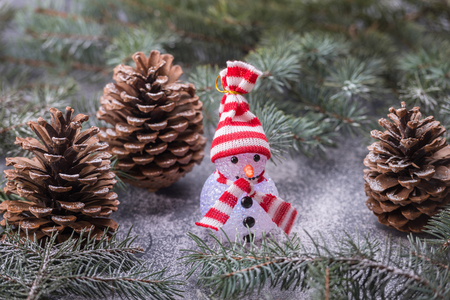 Snowman on background fir twigs and cones. New Year card concept