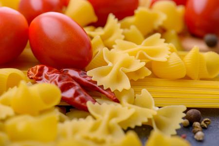 stirred: Closeup raw pasta and tomatoes. Italian food concept