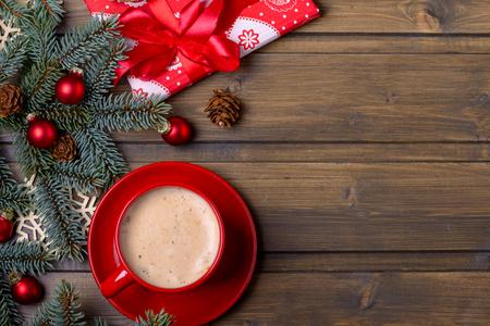 赤カップと赤いギフトボックスにコーヒー。木製の背景にモミとコーンの木