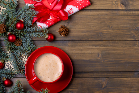 Coffee in red cup and red gift box. Fir and cones tree on wooden background Фото со стока