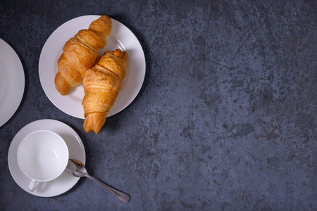 Traditional croissants and empty cup for tea or coffee. Breakfast concept
