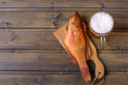 Smoked fish and fresh beer on wooden table. Copy space for text. Top view Stock Photo
