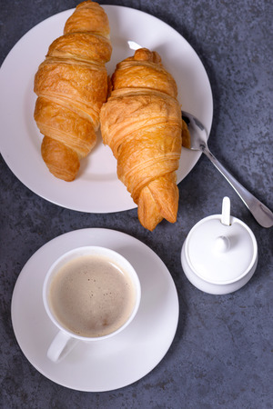 Closeup coffe with croissants on gray stone table. Top view