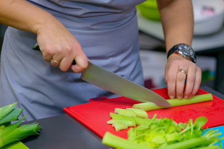 Woman cutting celery in kitchen. Concept preparing food