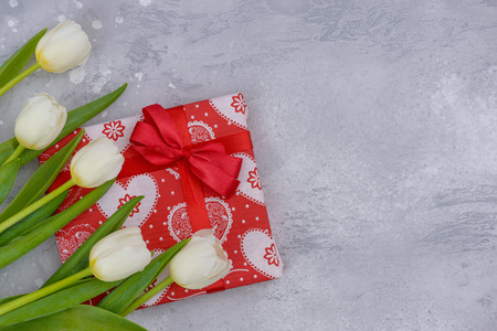 Greetings banner with white tulips and red gift box with copy space