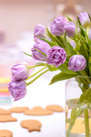 Close-up purple tulips in vase on table, template card greetings Stock Photo