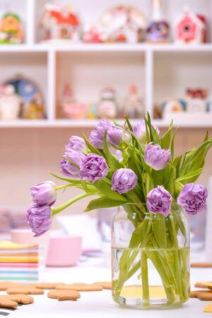 Purple tulips in vase on table in working atmosphere