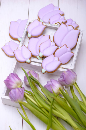 Gingerbread cookies in the shape of flower and purple tulip on wooden table
