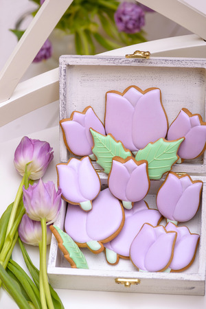 Purple gingerbread tulips cookie in wooden box with natural flowers. Holiday gift