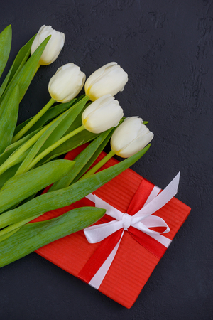 White tulips and red gift box on black background