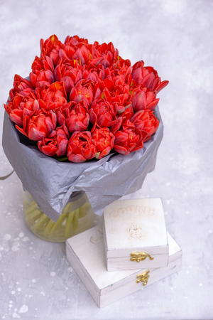 Brightly red bouquet tulips. On gray background with copy space Stock Photo