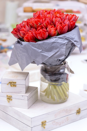 Bouquet red tulips and white boxs on table