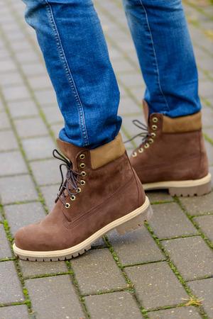 Winter boots on mens legs. On the sidewalk
