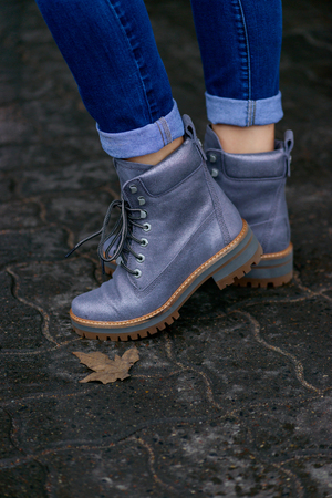 Gray stylish womans boots in street autumn