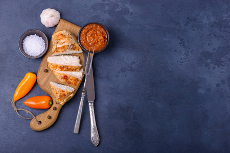 Slice chicken on fork. On food background with copy space