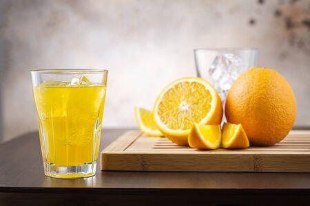 Orange fizzy lemonade in glass on background fresh orange fruit. Vegetarian and organic drink Stock fotó
