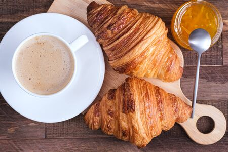 Directly above cap coffee cappuccino and croissant and jam. French breakfast on wooden table