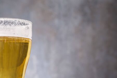 Close-up light beer in glass on gray background with copy space 版權商用圖片
