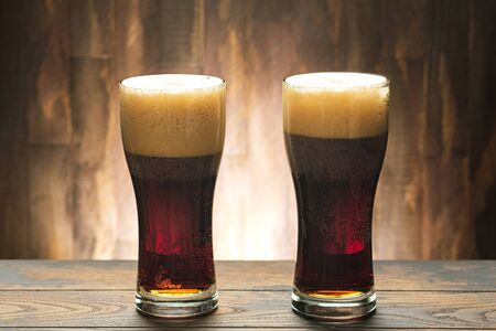 Two full glass with dark beer and foam on wooden background