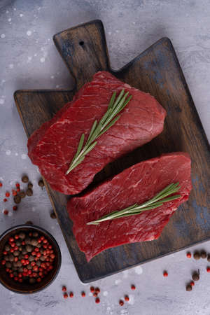 Uncooked beef meat with spices and rosemary on cutting board. Cooking steak Stock Photo