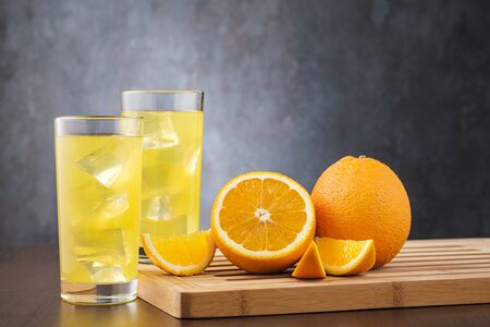 Two glass with orange juice and copy space for text. On gray stone background and fresh orange fruit