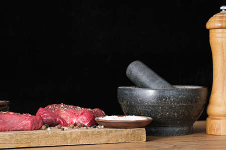 Raw beef and spices salt and pepper seasoning on cutting board and black background