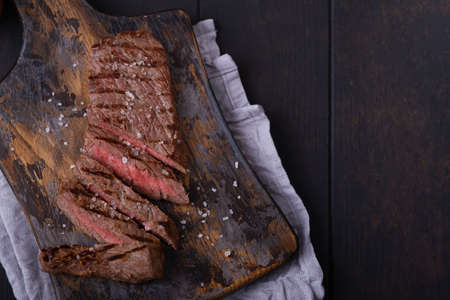 Directly above sliced beef steak seasoned with salt on cutting board with copy space Stock Photo