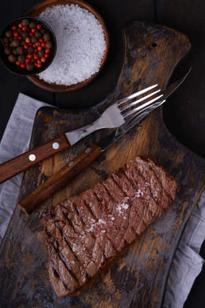Grilled beef steak with knife and fork on cutting board. Cooked food Stock Photo