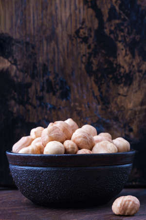 full bowl of hazelnuts on table with copy space on wooden backgrounds