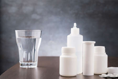 Glass water and medicament for arvi or flu on table. Copy space for text Imagens