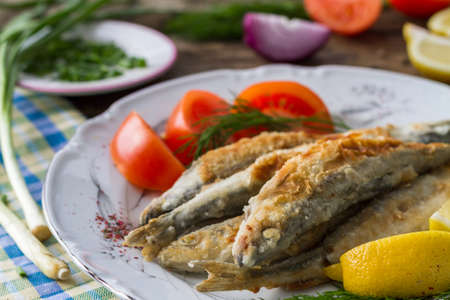 Fried fish smelt on a plate, served with lemon, tomatoes, onions and herbs.