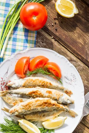 smelt: Fried fish smelt on a plate, served with lemon, tomatoes, onions and herbs.