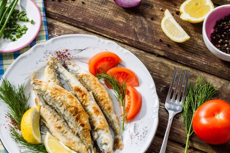 fish plate: Fried fish smelt on a plate, served with lemon, tomatoes, onions and herbs.