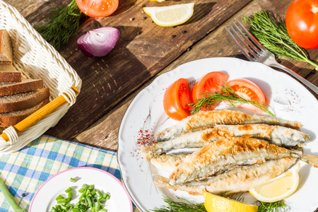 pescado frito: Fried fish smelt on a plate, served with lemon, tomatoes, onions and herbs.