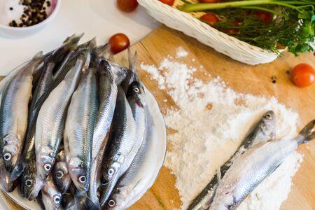 Fresh fish smelt with flour on a cutting board.